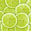 Abstract green background with citrus-fruit of lime slices — Stock Photo