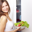 Young woman with healthy salad. background refrigerator — Stock Photo #6027511