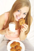 Teenage girl with a glass of milk and cookies — Stock Photo