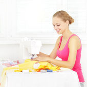 Girl using sewing machine to sew clothing — Stock Photo