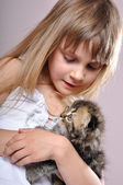 Child cuddling a kitten — Stock Photo