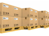 Stacks of cardboard boxes on shipping pallets — Stock Photo