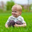 Smiling little boy sitting in fresh grass — Stock fotografie