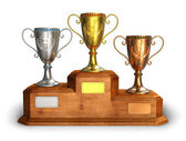 Gold, silver and bronze trophy cups on pedestal — Stock Photo