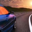 Blue car driving by autobahn in sunset with motion blur — Stock Photo