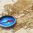 Blue metal compass on the old world map — Stock Photo