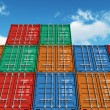 Stacked color cargo containers over the blue sky — Stock Photo