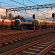Freight trains with fuel tank cars in sunset — Stock Photo
