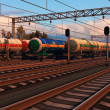 Freight trains with fuel tank cars in sunset - Stock Photo
