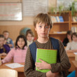 Serious schoolboy in front of class — Stock Photo
