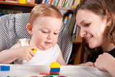 Mother playing with her son in blocks — Stock Photo