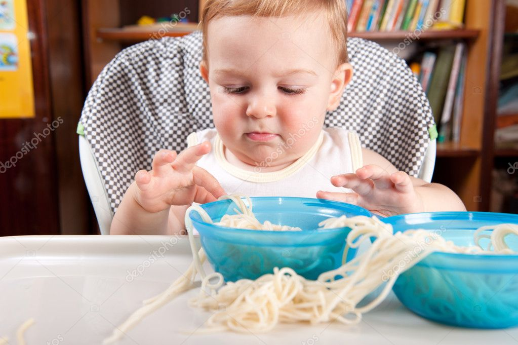 Serious boy is playing with long pasta — Stock Photo #6012866