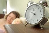Chica y reloj despertador — Foto de Stock