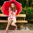 Young girl with umbrella in park — Stock Photo