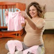 Pregnant woman with baby's dress — Stock Photo