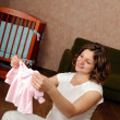 Pregnant woman with baby's clothes — Stock Photo #6449979