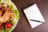 Restaurant table with roast chicken, notebook and pen — Stock Photo