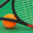 Tennis racket and  ball on green background — Stock Photo #5419377