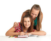 Two teenage girls smiling and reading book — Stock Photo