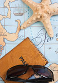 Passport and sunglasses on map — Stock Photo