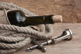 Old corkscrew and bottle of wine — Stock Photo