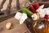 Vegetables and bottle of cooking oil in a basket — Stock Photo