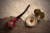 Compass and a tobacco pipe on a wooden board — Stock Photo