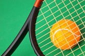 Tennis racket and ball on green background — Photo