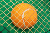 Orange tennis ball on green background — Stock Photo