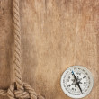 Compass and rope knot on wooden background — Stock Photo