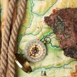 Stock Photo: Compass with rope and stone on topographic map