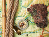 Compass with a rope and a stone on topographic map — Stock Photo