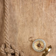 Compass and rope on a wooden background — Stock Photo