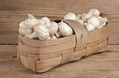 Basket with mushrooms on wooden background — Stock Photo