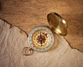 Compass and a piece of old paper — Stock Photo