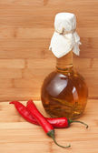 Red chili peppers and a bottle of spiced — Stock Photo