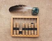 Oude glazen inktpotje met een ganzenveer en abacus op houten tafel — Stockfoto