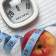 Apple and measuring tape on the floor scales - Photo