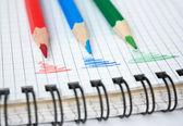 Červené, zelené a modré tužka na Poznámkový blok — Stock fotografie