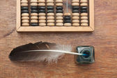 Old glass inkwell with a quill pen and abacus on wooden table — Stock Photo