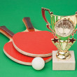 Stock Photo: Sports awards and tennis racquets on green table