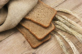 Slices of rye bread and ears of corn — Stock Photo