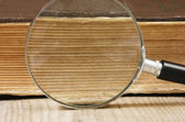 Old book and magnifying glass — Stok fotoğraf