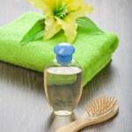 Bottle hairbrush towel and flower — Stock Photo