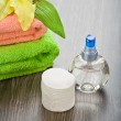 Bottle towels flower and cotton pads on wooden background — Stock Photo #5397463