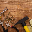 Photo: Hamer pliers screwdriwer and gloves on woodn board