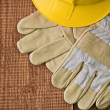 View on a hardhat with gloves on wooden board — Stock Photo