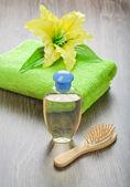 şişe saç fırçası havlu ve çiçek — Stok fotoğraf