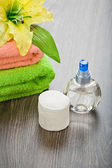 Bottle towels flower and cotton pads on wooden background — Stock Photo