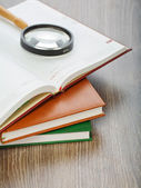 Diaries and magnifier on wooden background — Stock Photo